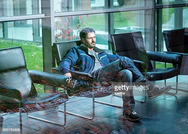 mature man sitting behind window waitingin lobby