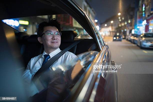 Mature  man sitting in a back seat of the car