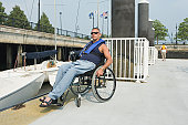 Disabled man sitting in a wheelchair at a harbor for adaptive sailing