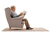 Mature man sitting in an armchair and reading a newspaper isolated on white background