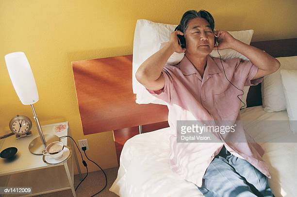 Mature Man Sitting in Bed and Listening to Music on Headphones With His Eyes Closed