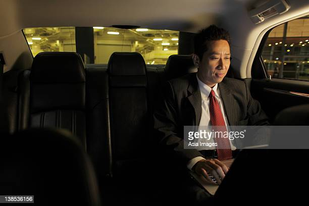 Mature man sitting in car working on laptop
