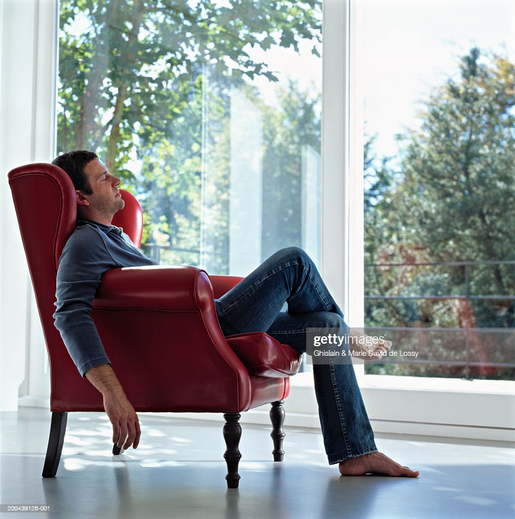 Mature man sitting in chair barefoot, eyes closed, side view : Stock Photo