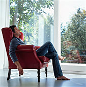 Mature man sitting in chair barefoot, eyes closed, side view