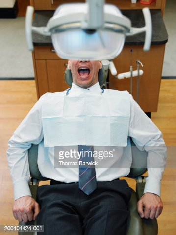 Mature man sitting in dentist's chair, mouth open, elevated view
