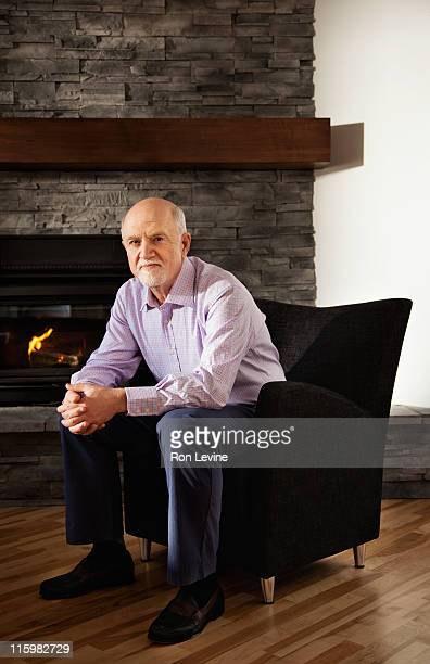 Mature man sitting in front of his fireplace