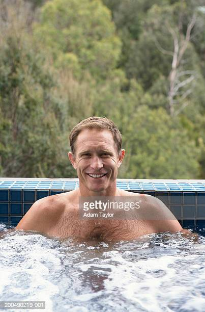 Mature man sitting in hot tub, smiling, portrait