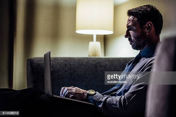 Mature man sitting in sofa and working on laptop