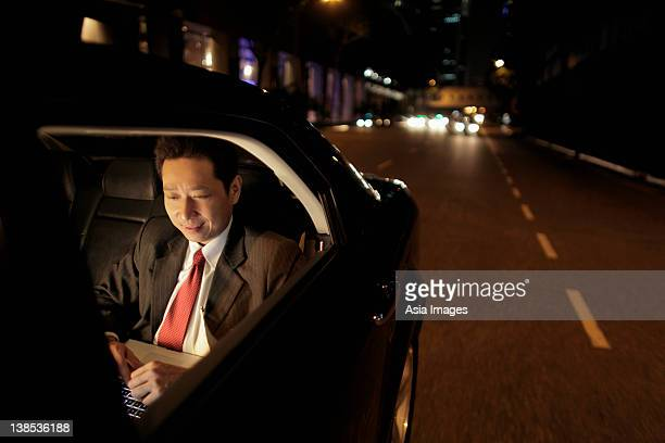 Mature man sitting in the back seat of a care working on a laptop
