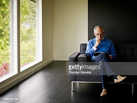 Mature man sitting looking at digital tablet
