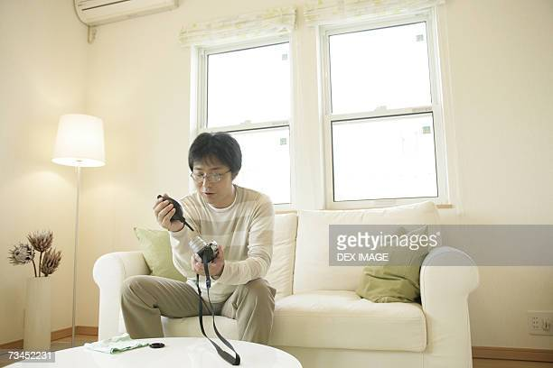 Mature man sitting on a couch and cleaning the lens of a camera