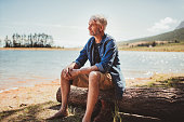Portrait of a mature man sitting on a log near the lake. Senior caucasian man sitting alone on the lake and looking at a view on a summer day.