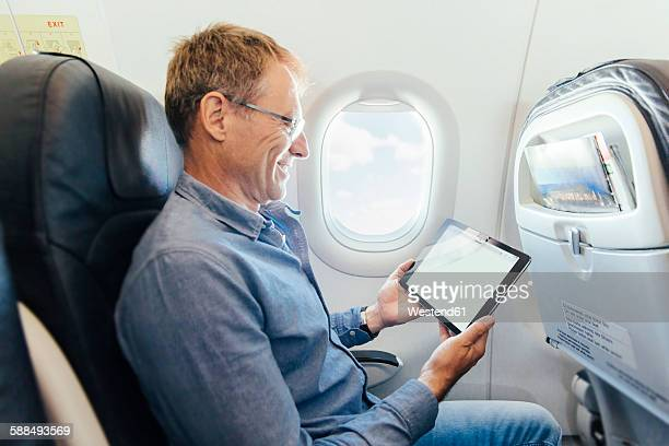 Mature man sitting on an airplane looking at his digital tablet