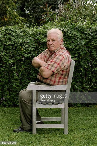 Mature man sitting on chair in backyard, arms crossed
