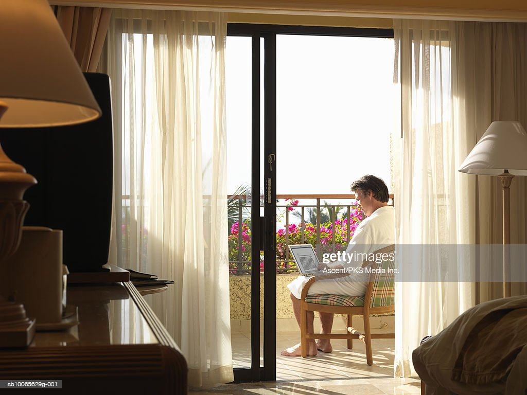 Mature man sitting on chair in balcony, using laptop : Stock Photo
