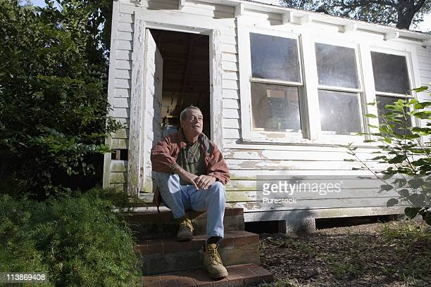 Mature man sitting on doorstep of dilapidated tool shed