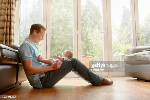 Mature man sitting on floor with baby son on his lap
