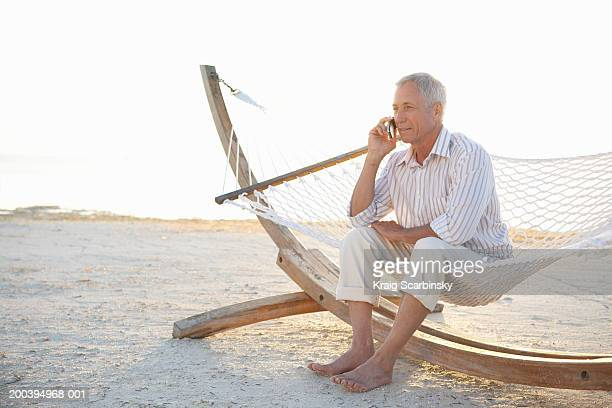 Mature man sitting on hammock on beach, using mobile phone, smiling