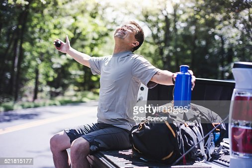 Mature man sitting on pick up truck with arms out