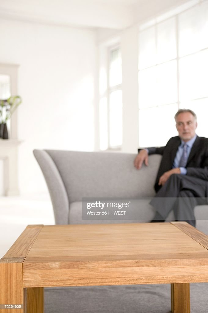 Mature man sitting on sofa, looking away (focus on table in foreground)
