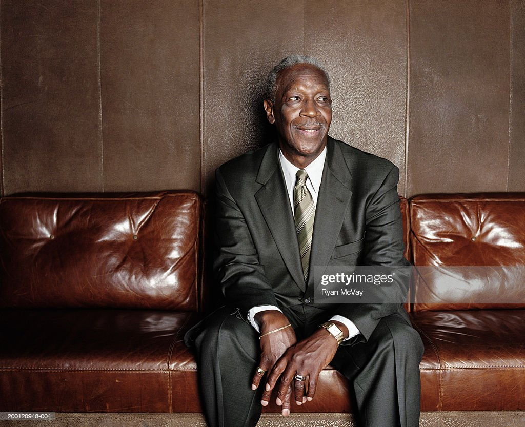 Mature man sitting on sofa, smiling