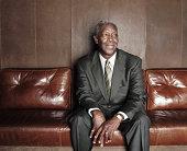 Mature man sitting on sofa, smiling
