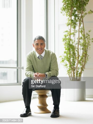 Mature man sitting on stool in commercial interior, portrait : Stock Photo