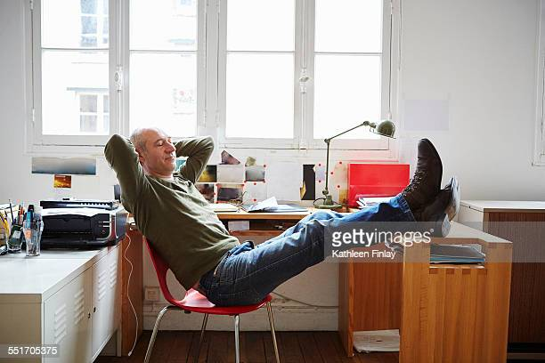 Mature man sitting with feet up at desk