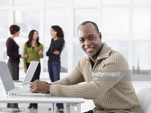 Mature man sitting with laptop in office, smiling, portrait