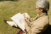 A Mature Man Sketching on the Lawn, Side View, High Angle View
