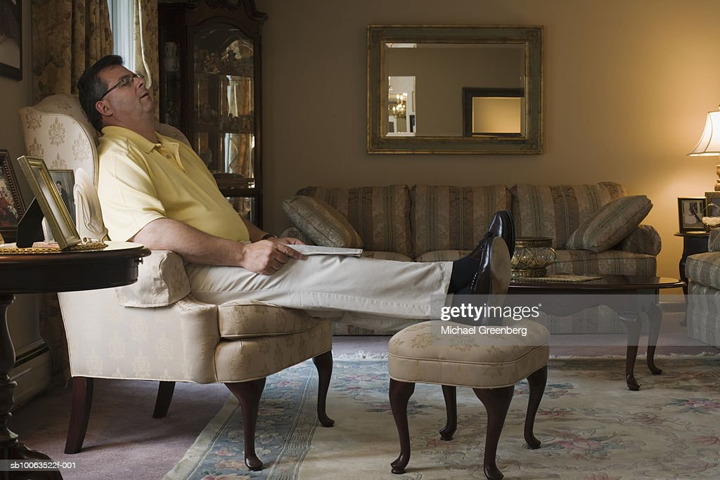 Mature man sleeping in armchair in living room, side view