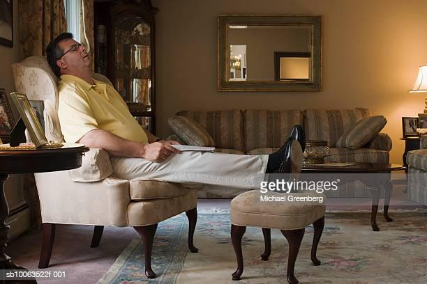 Mature man sleeping in armchair in living room, side view