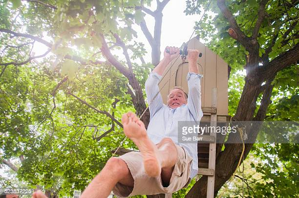 Mature man sliding down on pulley from tree house