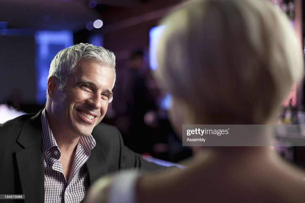 Mature man smiling at woman in a bar. : Stock Photo
