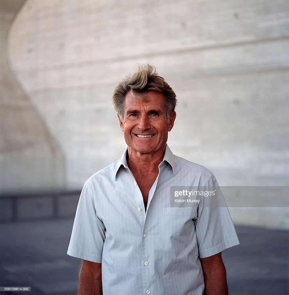 Mature man smiling outdoors, portrait : Stock Photo