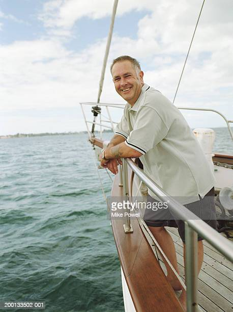 Mature man smiling, standing on bow of sailboat, portrait