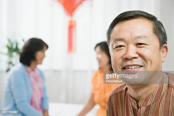 Mature man smiling, women in background