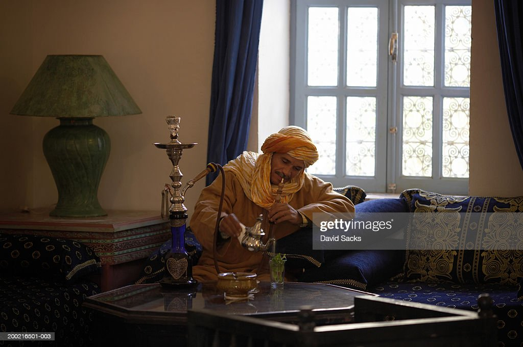 Mature Man Smoking Hookah Pipe In Living Room Pouring Tea Stock Photo