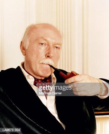 Mature man smoking pipe, close-up