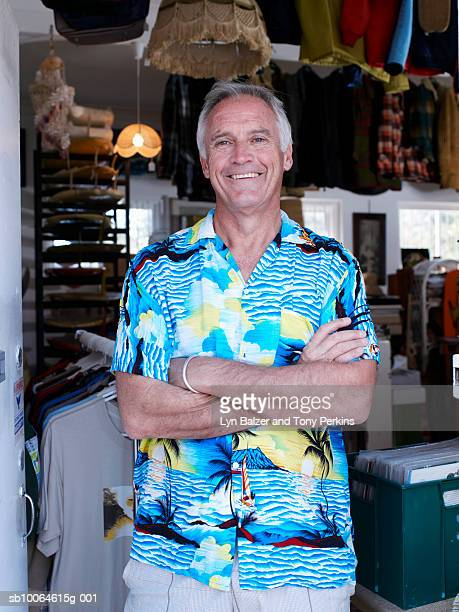 Mature man standing at clothes shop, smiling, portrait