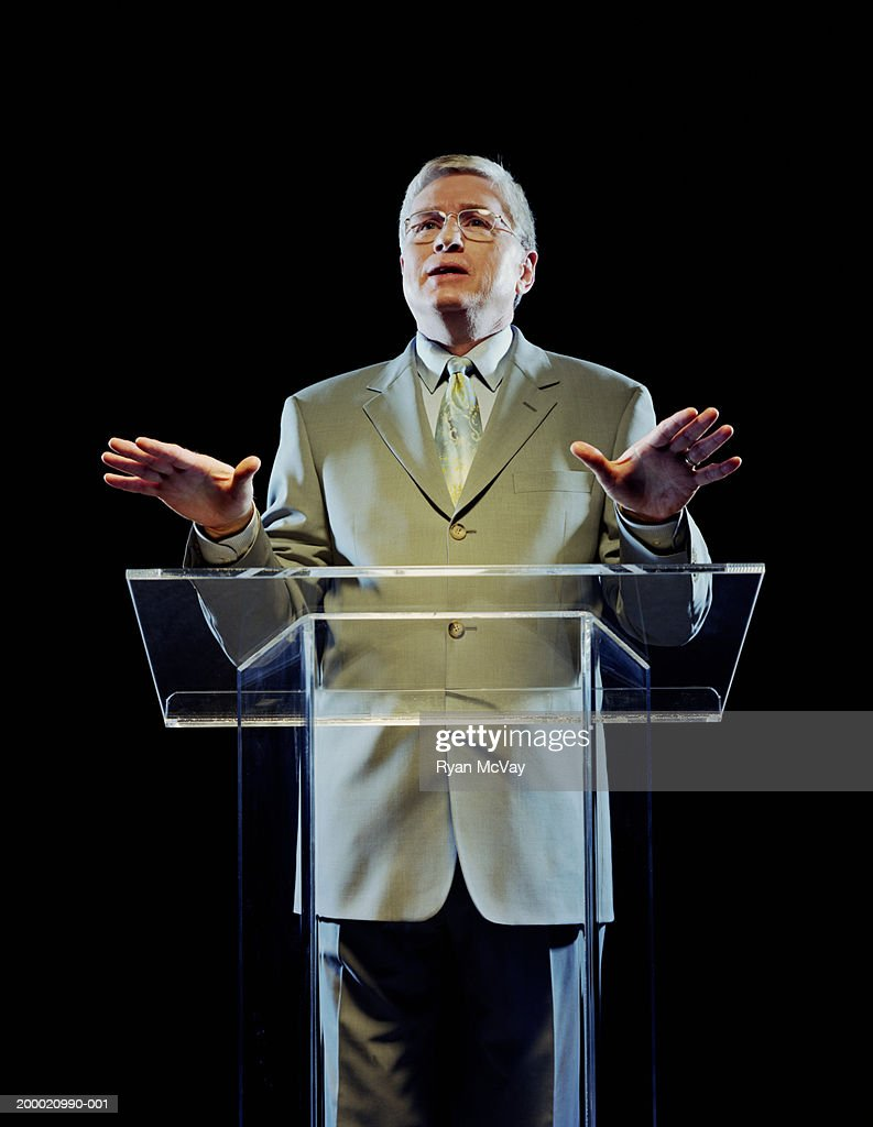Mature man standing at podium, giving speech : Stock Photo