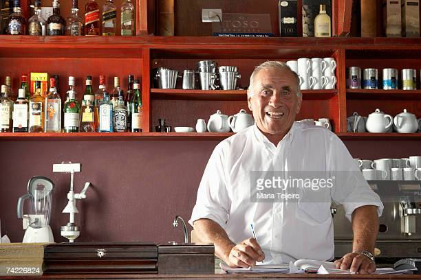 Mature man standing behind counter in cafe