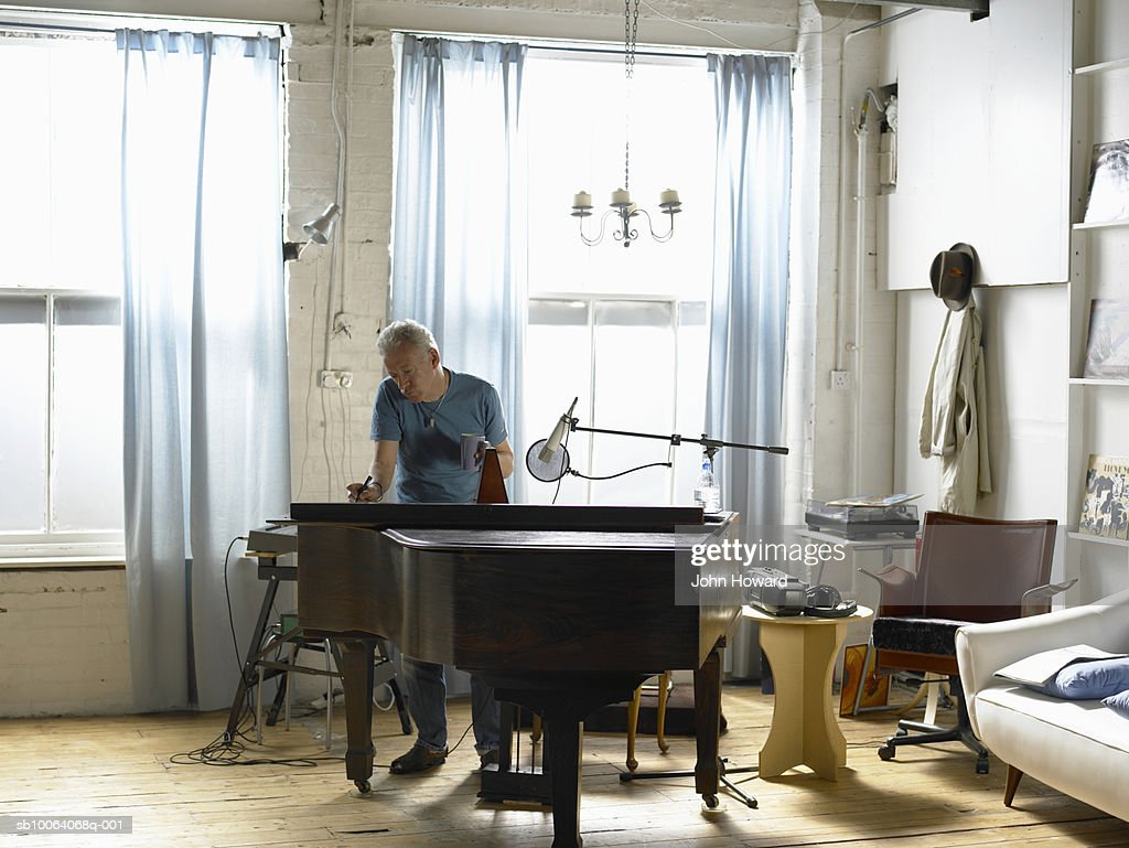 Mature man standing behind piano, writing