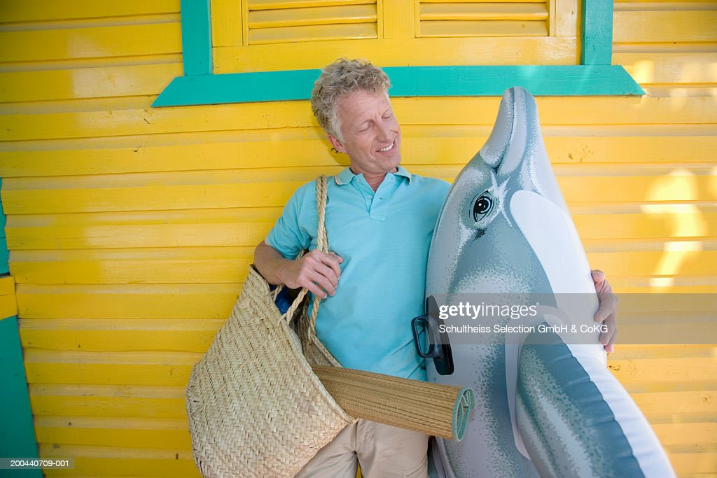 Mature man standing by beach hut holding inflatable dolphin, smiling : Stock Photo