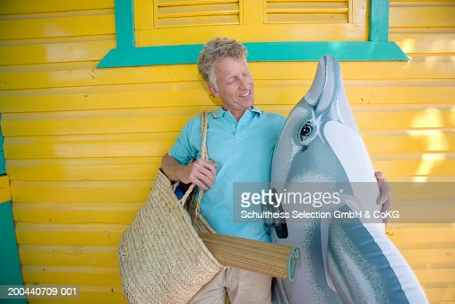 Mature man standing by beach hut holding inflatable dolphin, smiling : ストックフォト