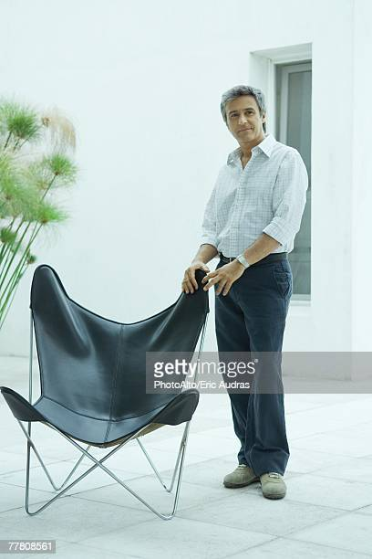 Mature man standing by chair, full length portrait