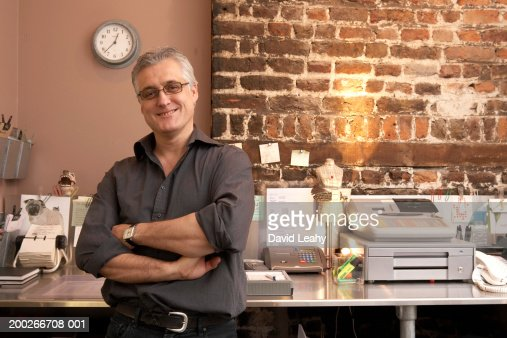Mature man standing by till, arms folded, smiling, portrait : Stock Photo