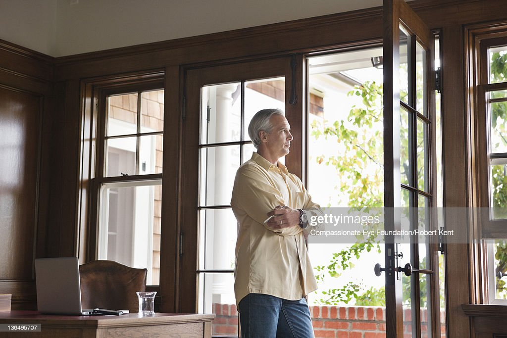 Mature man standing by window in home office : Stock Photo