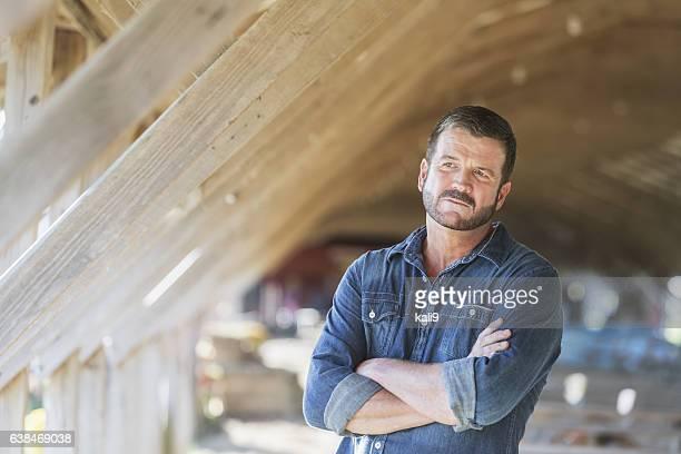 Mature man standing in barn