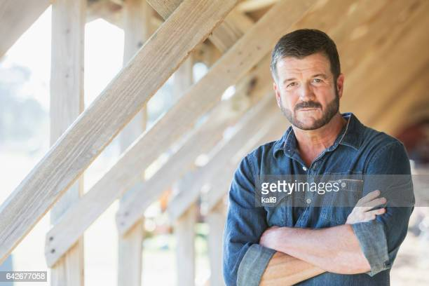 Mature man standing in barn